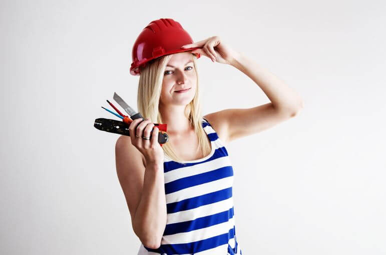 woman in red hard hat standing with tools in hand for chelsea lamb article diy home maintenance projects you cant afford to put off on reverse mortgage info site