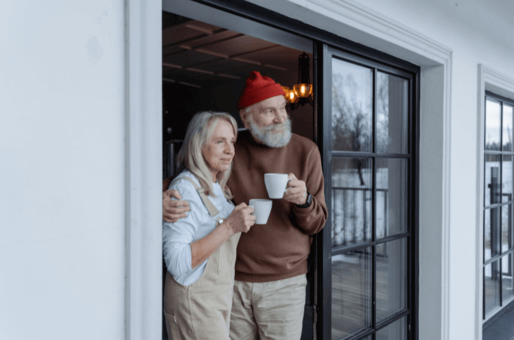 older man and woman standing at sliding glass door looking outside with a cup of coffee for kat sarmiento article three ways retiress an turn their home into a money making property