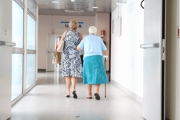 photo of two women walking down the hallway of a hospital for the article by chelsea lamb titleled Set a Strategy to Pay for Alzheimer's Care